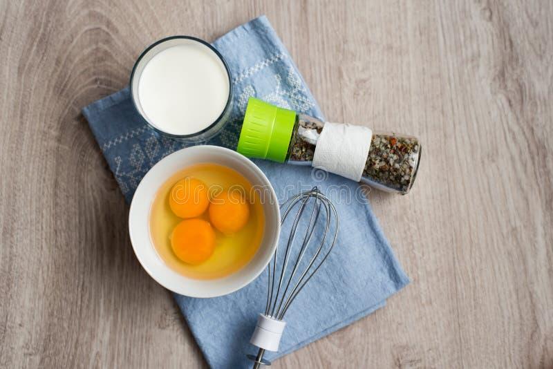 Wciąż życie produkty dla omletu, diet śniadaniowi jajka w filiżance, szkło mleko, set mieszane pikantność i blender na błękitnym  obraz royalty free