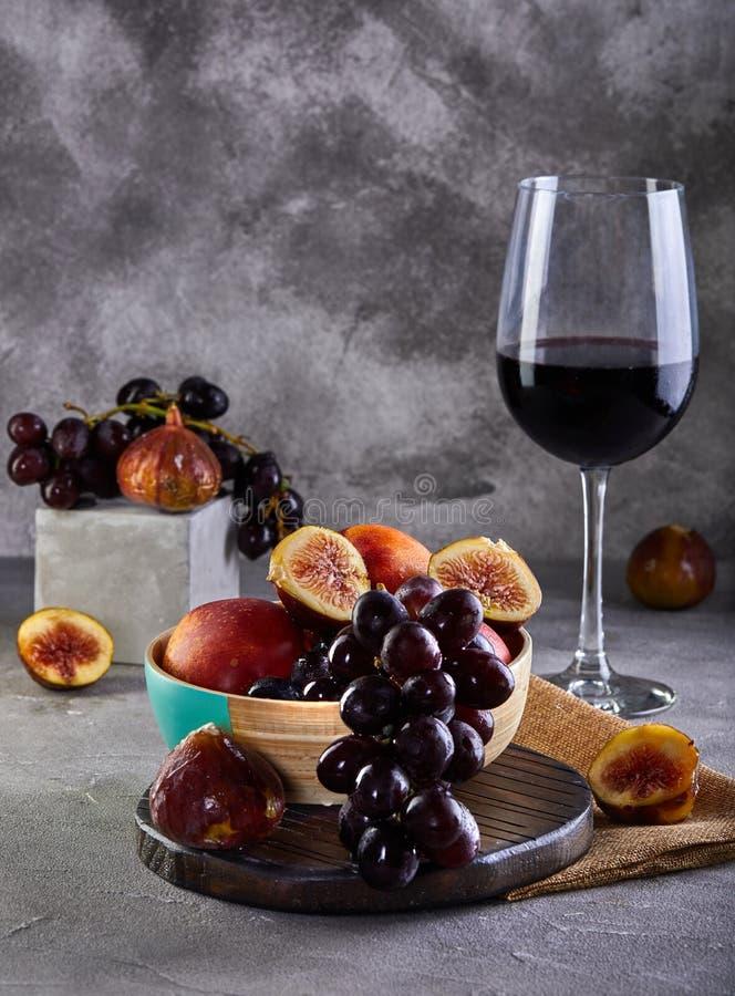 Wciąż życie winogrona, brzoskwinie, figi i szkła czerwone wino na szarości, obrazy royalty free