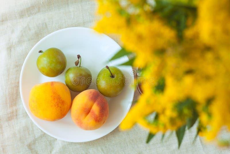 Wciąż życie z świeżymi brzoskwiniami i śliwkami na bieliźnianego płótna tle na drewnianym stole Jaskrawe soczyste lato owoc, flat zdjęcie royalty free