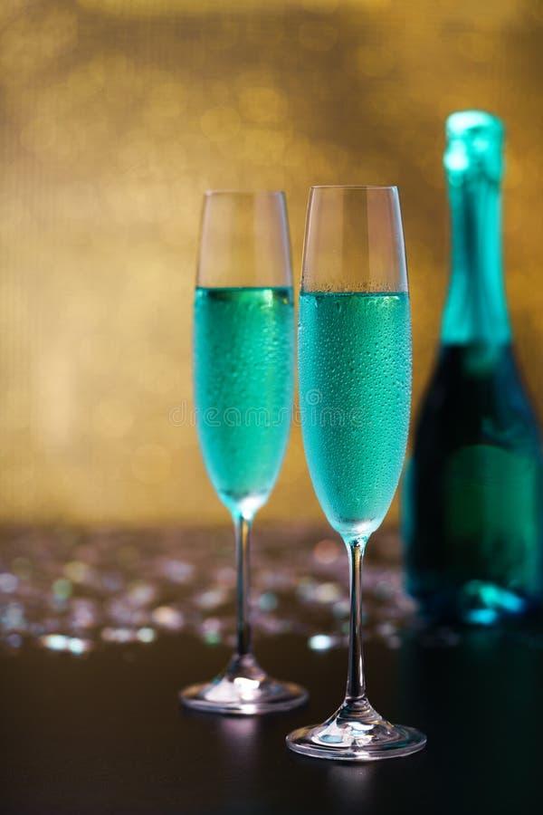Wciąż życie z błękitnym bokeh tłem, Sele szampana i złota/ zdjęcia royalty free