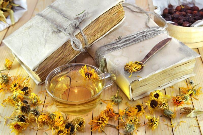 Wciąż życie z calendula herbatą i starymi książkami fotografia stock
