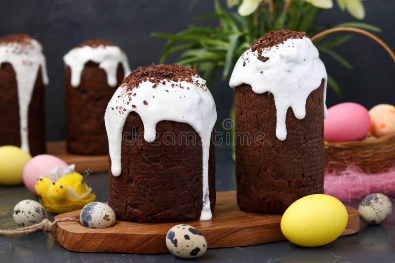 Wciąż życie z czekoladowymi wielkanoc tortami i kolorowymi jajkami na ciemnym tle obrazy royalty free