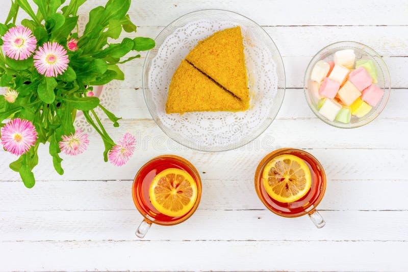 Wciąż życie z filiżankami herbata, kawałkami tort, bukietem różowi kwiaty w różowym garnku i marshmallows na białym drewnianym st zdjęcie royalty free