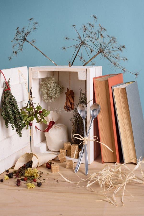 Wciąż życie z herbacianymi łyżkami, starymi książkami i pudełkowaty pełnym herbaciani ziele na drewnianym stole, turkusowy tło zdjęcia stock
