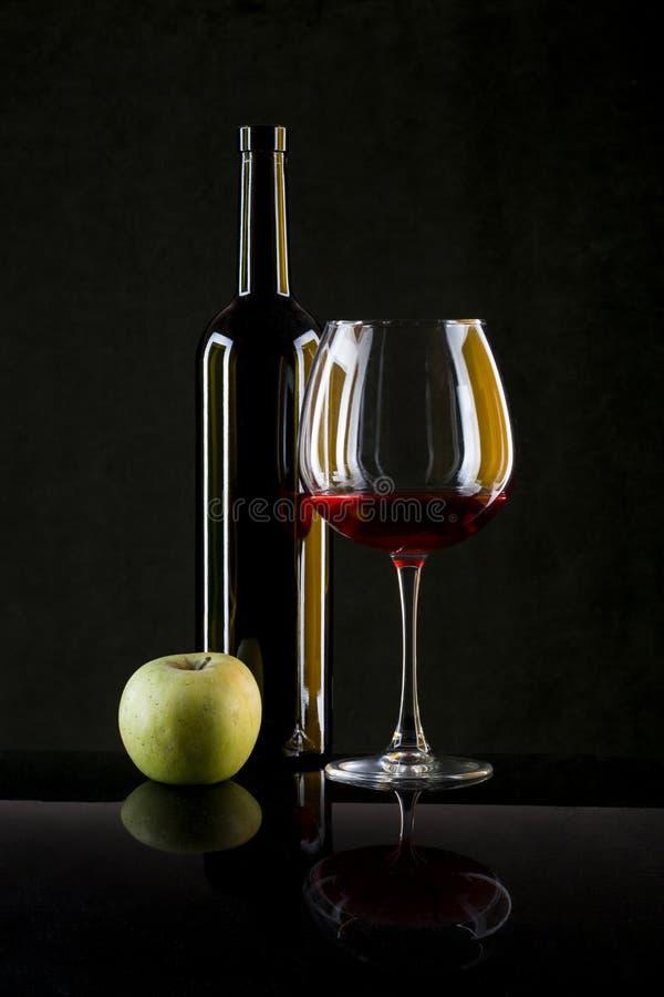 Wciąż życie z jabłkiem, butelką i szkłem wino, obrazy stock