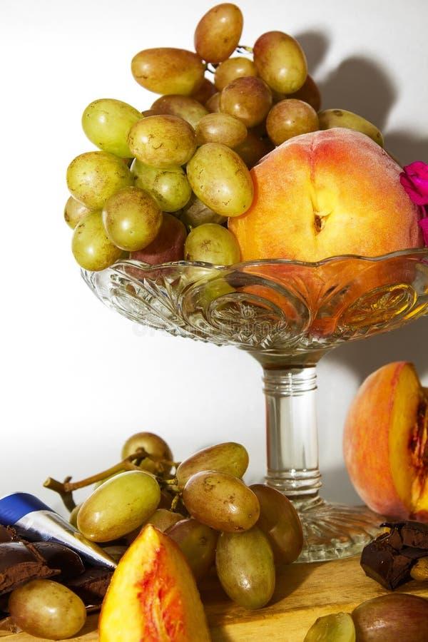 Wciąż życie z owocowymi brzoskwiniami i winogronami na szklanej wazie na tle popielatym lub srebnym obraz royalty free