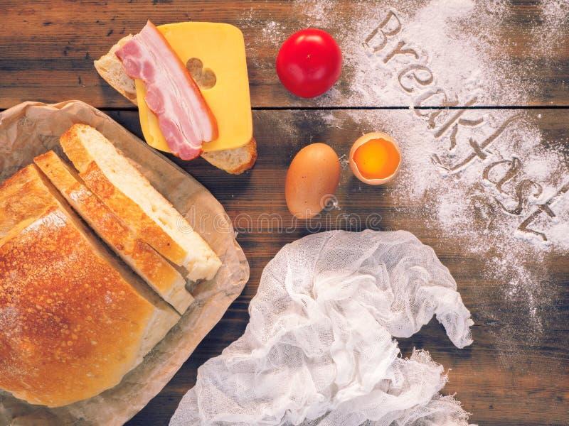 Wciąż życie z słowa śniadaniem na drewnianym stole, odgórny widok Świeży, pokrojony chleb z plasterkiem baleron, i ser zdjęcia stock