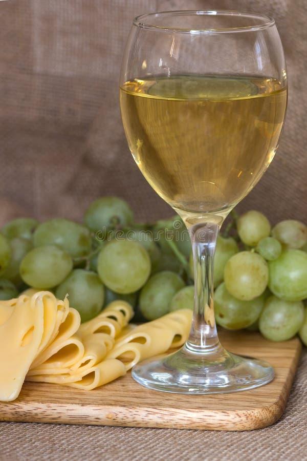 Wciąż życie z szkłem biały wino, ser i winogrona, fotografia stock
