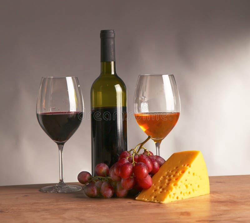 Wciąż życie z szkłem i butelką wino, ser i winogrona, obrazy royalty free