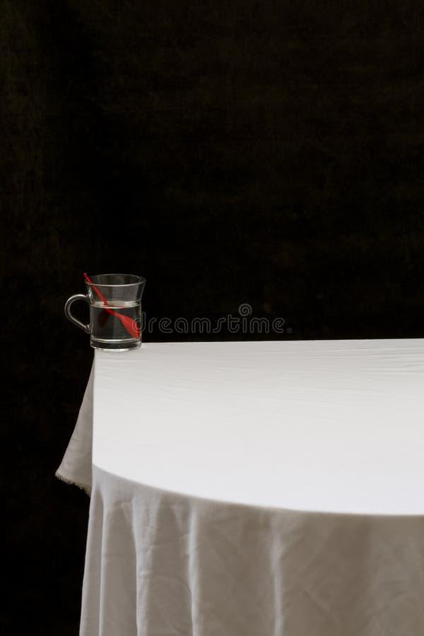 Wciąż życie z szkłem wodne i czerwone łyżki zdjęcie royalty free