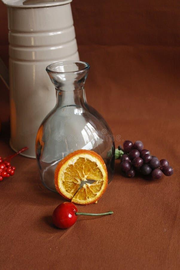 Wciąż życie z szklaną wazą z podlewanie puszką i pomarańczowym plasterkiem obraz royalty free