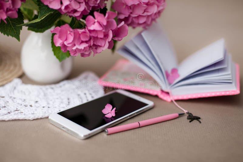Wciąż życie z telefonem komórkowym, hortensja kwiatami, otwartym żeńskim notatnikiem i menchii piórem, zdjęcia royalty free