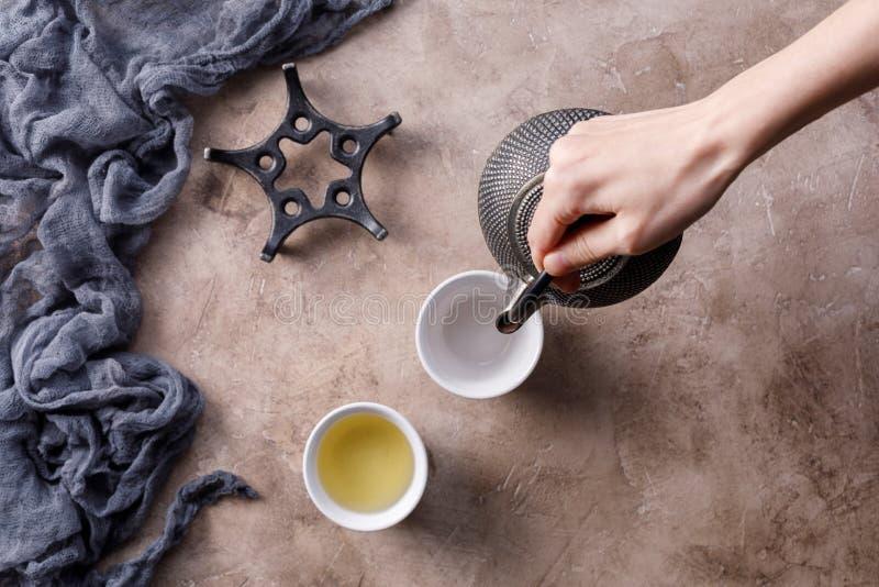 Wciąż życie z tradycyjną Azjatycką ziołową herbatą która nalewają od starego żeliwnego czajnika na textured tle z pialami, obraz stock