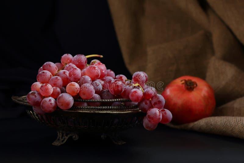 Wciąż życie z wazą winogrona i granatowiec na ciemnym tle obrazy royalty free