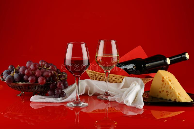 Wciąż życie z winem, serem i winogronami na czerwonym tle, obraz royalty free