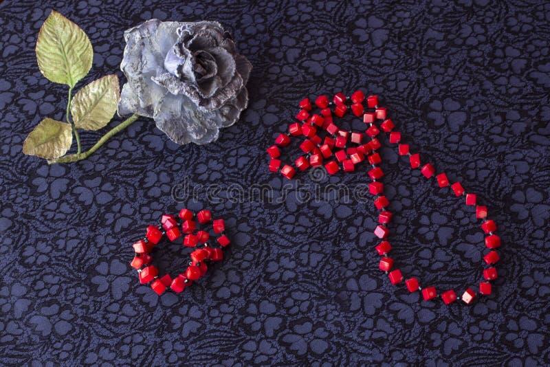 Wciąż wzrastał z czerwonymi koralikami i bransoletką na tekstylnym tle życie sztuczny obraz stock