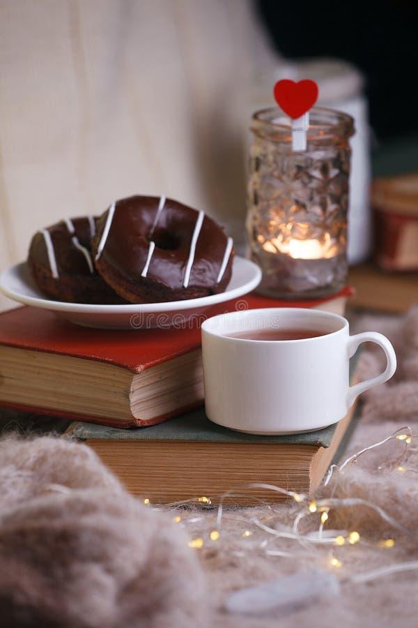 Wci?? ?ycie szczeg??y w domowym wn?trzu ?ywy pok?j Filiżanka herbata, pączki, książki, woolen szkocka krata i świeczka na drewnia zdjęcie royalty free