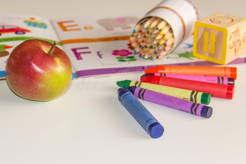Wczesne dzieciństwo uczenie z książką i kredkami obraz stock
