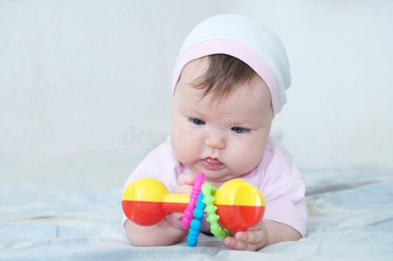 Wczesny Móżdżkowy rozwój skoncentrowana mała dziewczynka bawić się z brzękiem fotografia royalty free