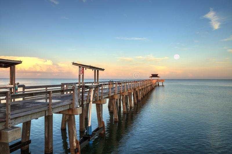Wczesny moonset i wschód słońca nad Naples molem na zatoki wybrzeżu Naples, Floryda zdjęcie stock
