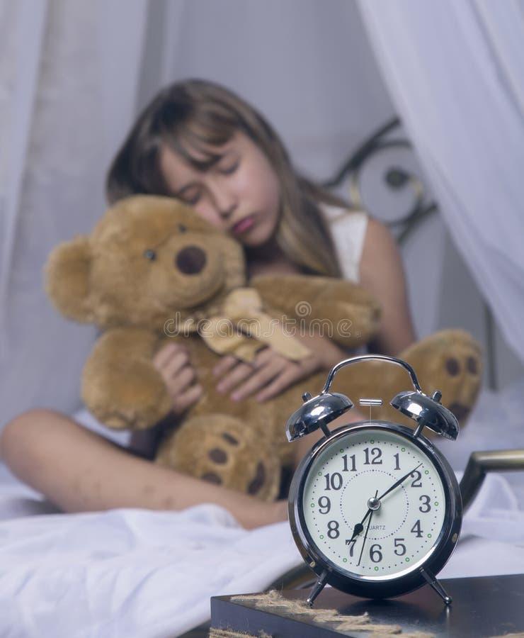 Wczesny obudzenie Budzik pozycja na wezgłowie stole Budził się uśpiony młodej dziewczyny mienia miś w łóżku na a fotografia stock