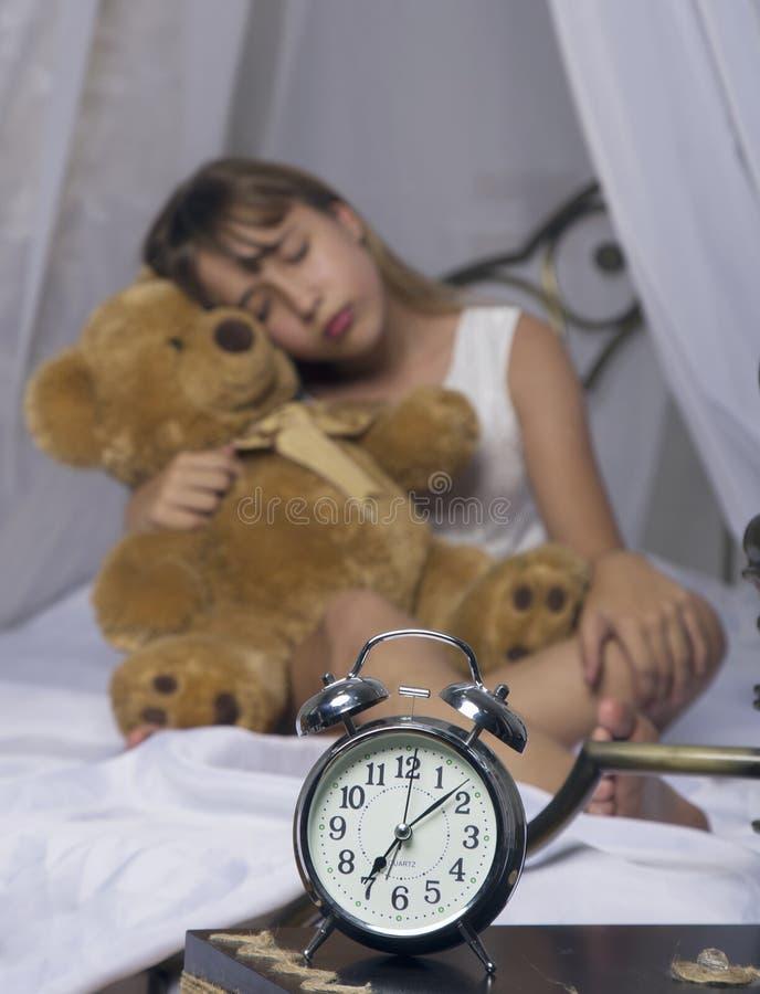 Wczesny obudzenie Budzik pozycja na wezgłowie stole Budził się uśpiony młodej dziewczyny mienia miś w łóżku na a zdjęcia royalty free