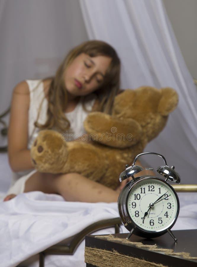 Wczesny obudzenie Budzik pozycja na wezgłowie stole Budził się uśpiony młodej dziewczyny mienia miś w łóżku na a obrazy stock