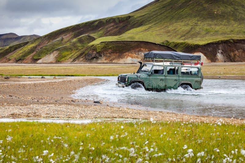 4WD de auto waadt rivier in Landmannalaugar in IJsland stock foto's