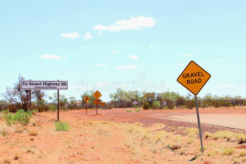 4wd gravel road, traffic warning signs, desert Australia. Warning signs at a 4wd gravel road to Stuart Highway, Outback wilderness of Australia royalty free stock images