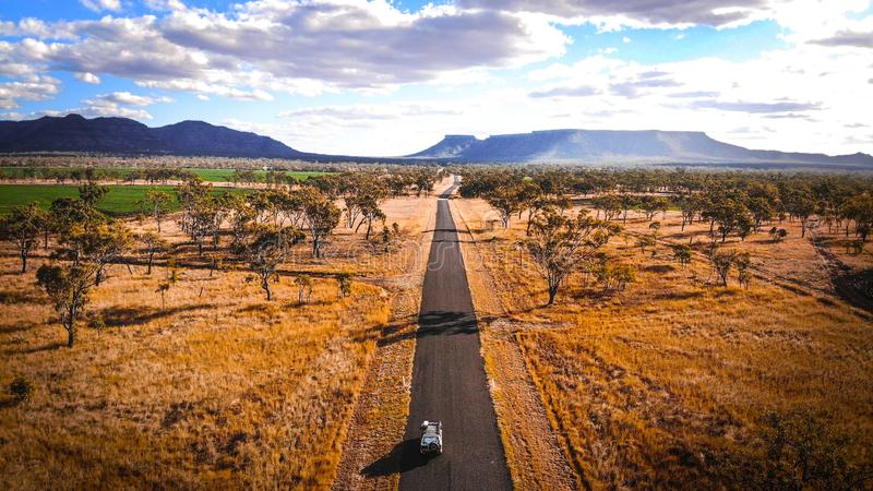 4wd Road Trip jeep journey to Ayers Rock through the rural Outback Australia valleys in desert land with mountains in the backgrou stock image