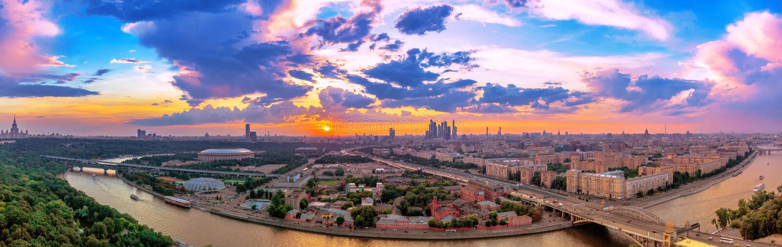 Wde angle vibrant panoramic view of sunset above Moscow city and cloud reflections in river with traveling boats and bridge stock photos