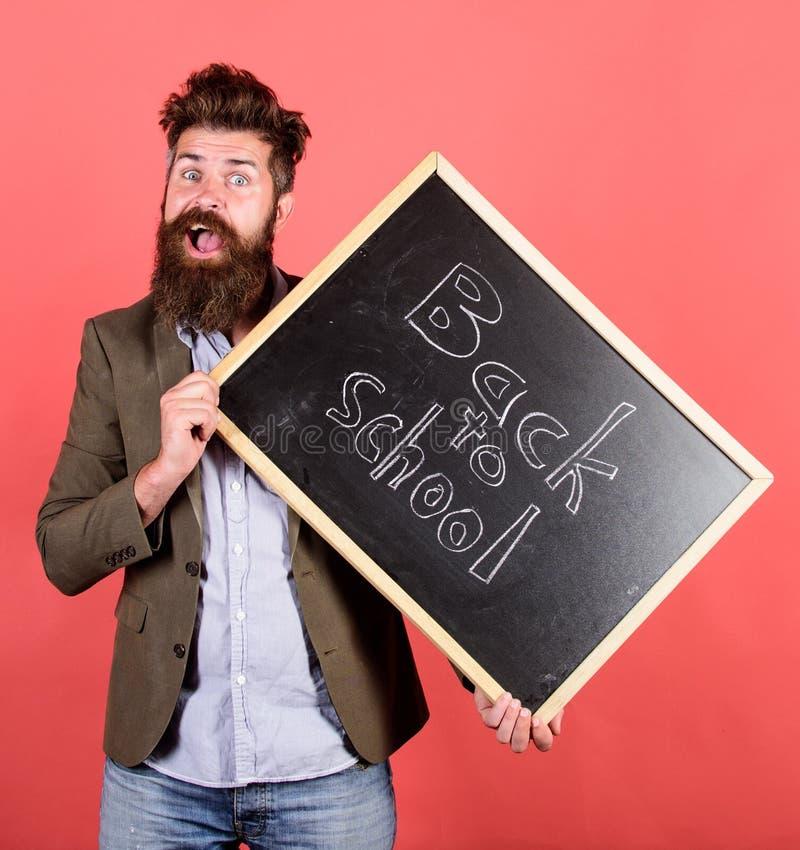 weź łatwe Nauczyciela brodaty mężczyzna trzyma blackboard z inskrypcją z powrotem szkoły czerwieni tło Nauczyciel z kudłacący obraz royalty free