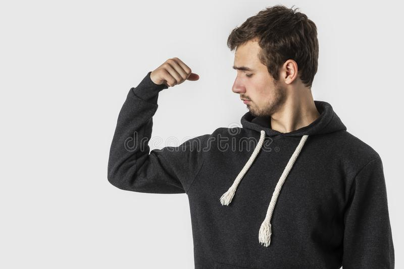 Weak caucasian young man looks at his biceps disappointedly. Isolated on white background. Weakness concept.  stock photography