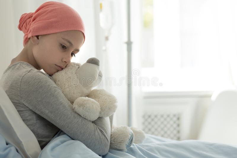 Weak girl with cancer wearing pink headscarf and hugging teddy bear royalty free stock images