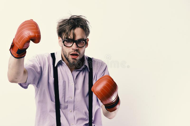 Weak guy makes hits and punches. Man with bristle and dull face wears boxing gloves stock photography