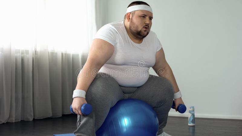 Weak obese male struggling to lift dumbbells, lack of physical activity, diet. Stock photo royalty free stock photo