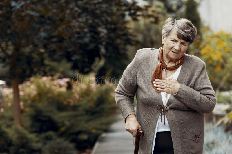 Weak senior woman with walking stick waiting for help during breathlessness attack. Weak senior woman with walking stick waiting for help during the stock photography