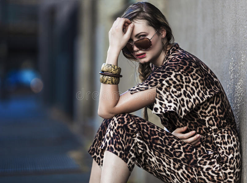 Weak woman sitting in the city and wearing a leopard-skin dress stock photography