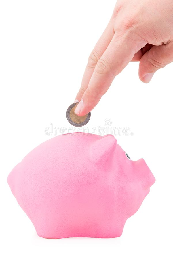 Wealth concept male hand puts coin in a piggy bank on a white stock photo