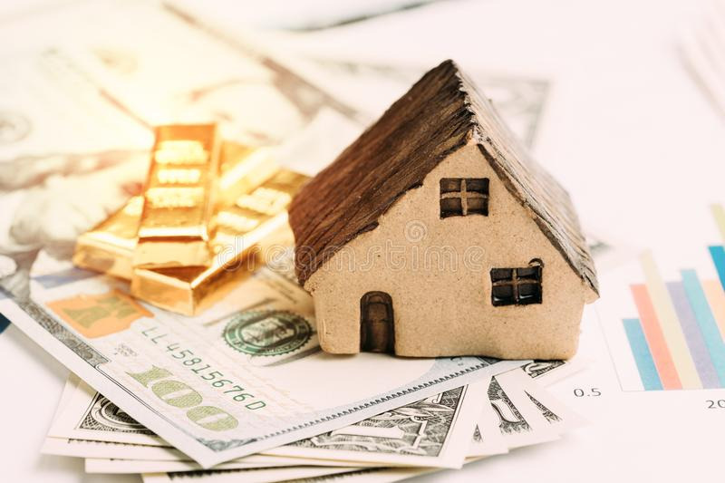 Wealth management or investment asset allocation concept, house, gold bars ingot on pile of US dollar bills on price bar chart us. Ing in balance risk and rich stock image