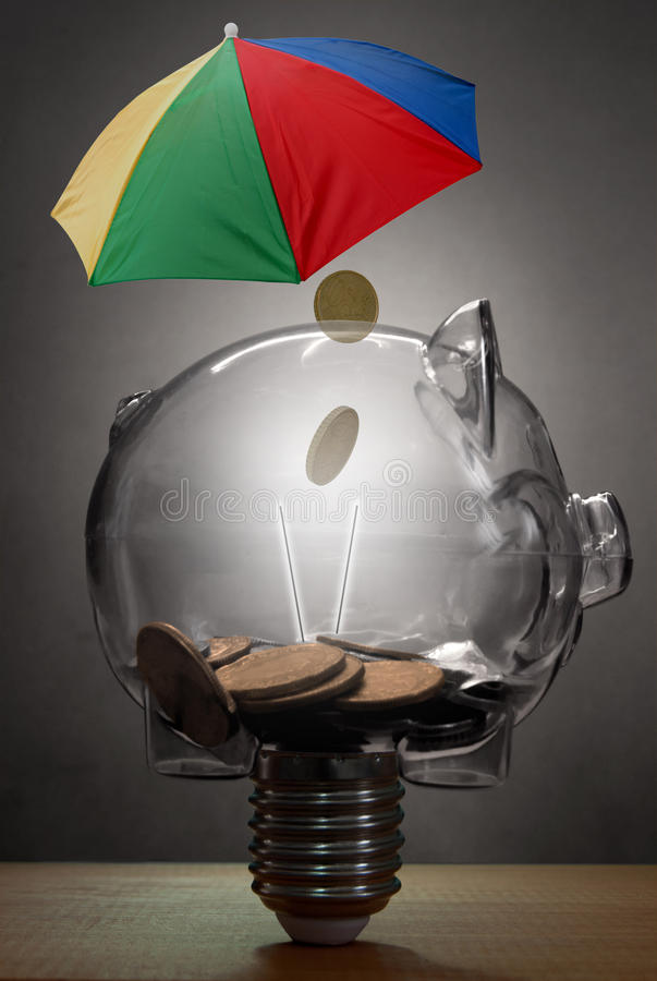 Wealth protection insurance concept. Piggy bank in the shape of a light bulb underneath an umbrella royalty free stock photo