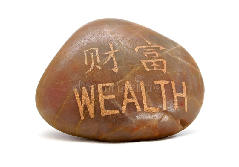 Wealth rock. Small rock with Wealth written in Chinese and English with gold lettering stock photography