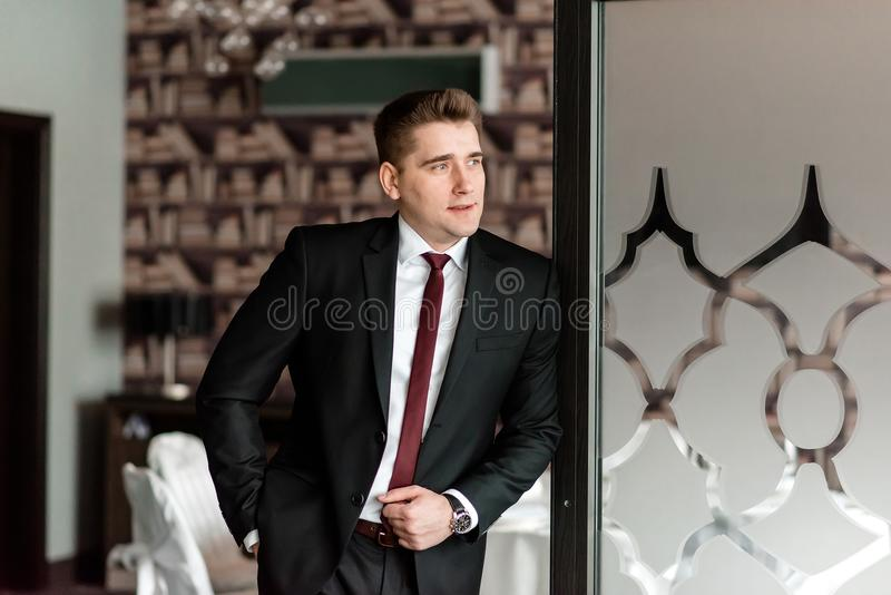Wealthy confident relaxed young man in black shirt stock image