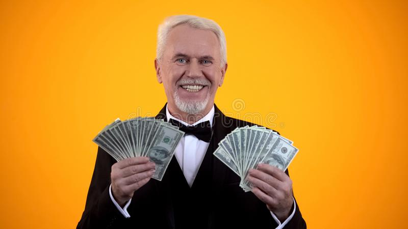 Wealthy elderly man in suit holding dollars and smiling, successful business royalty free stock photography