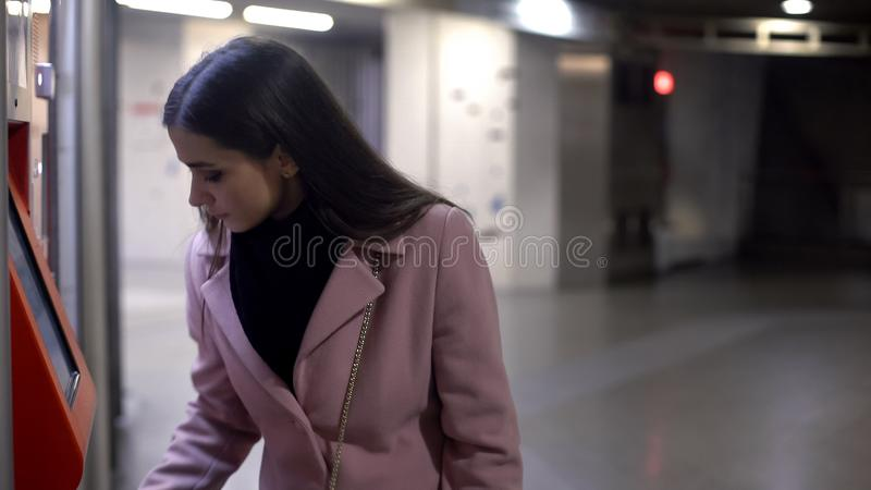 Wealthy woman withdrawing money in ATM at night time, finance, crime risk royalty free stock images
