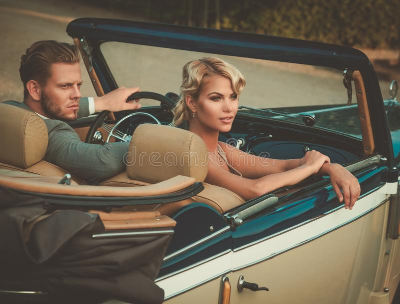 Wealthy young couple in a classic convertible royalty free stock photo