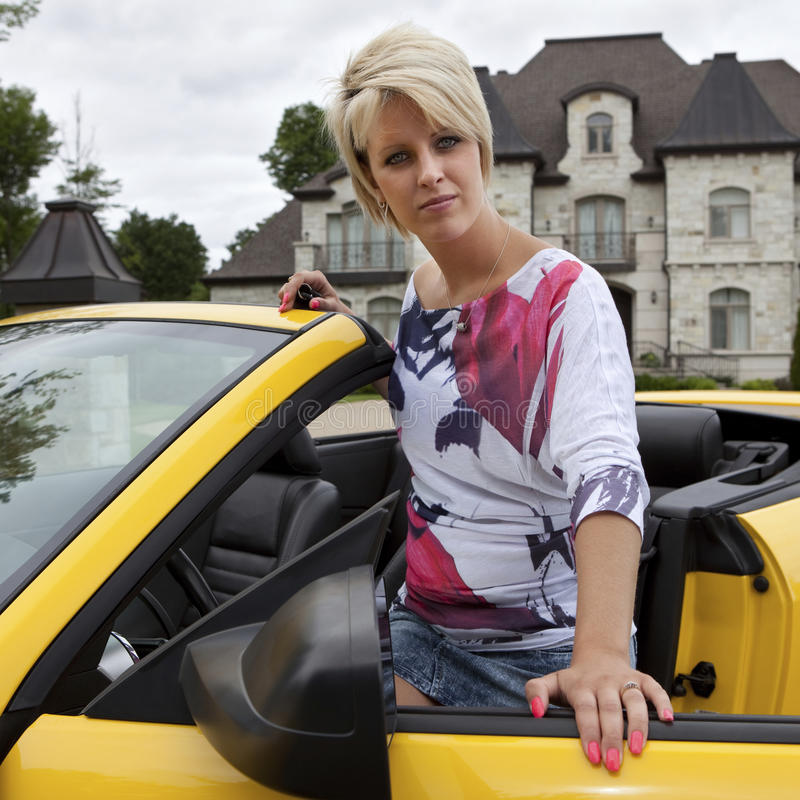 Wealthy young woman getting into a car royalty free stock photo