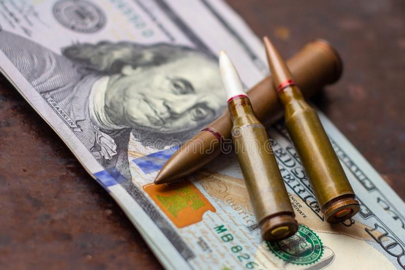 Weapon bullets on American dollars background. Military industry, war, global arms trade and crime concept. Weapon bullets on American dollars background royalty free stock photo