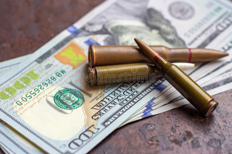 Weapon bullets on American dollars background. Military industry, war, global arms trade and crime concept. Weapon bullets on American dollars background stock images