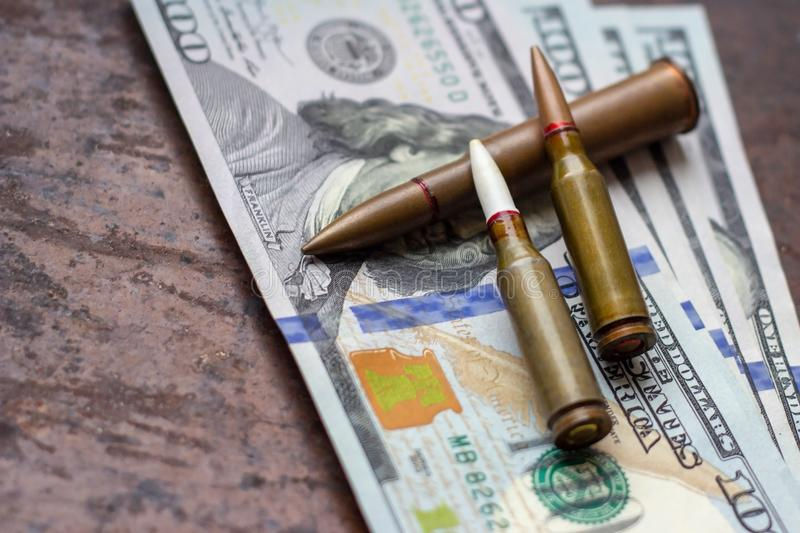 Weapon bullets on American dollars background. Military industry, war, global arms trade and crime concept. Weapon bullets on American dollars background stock image